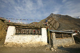 praying wheels and flags in muktinath, annapurna, nepal poster