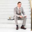 Портрет веселый бизнесмен сидит на шагах, имеющих документы в его руках...