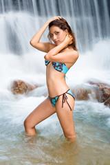 asian woman relaxing at the tropical water fall in bikini