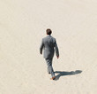 A business man walking in a desert with a clear shadow