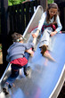 Girl helps brother up the playground slide
