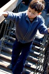 Little boy  walking across a suspended bridge