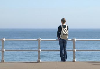 Chica con mochila mirando al mar
