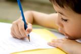 Fototapety  boy enjoying his his writing as part of homework,