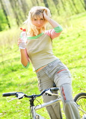 Beautiful young woman relaxing after riding a bike