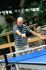 Active senior gentleman playing indoor table tennis