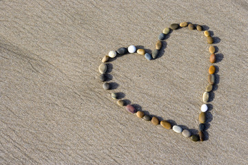 Heart made with small stone in the wet sand