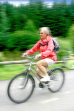 Mature woman enjoying a fast ride on her bike,