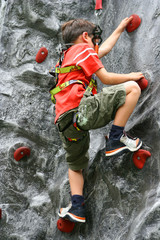Young boy climbing up the indoor rockclimbing wall.