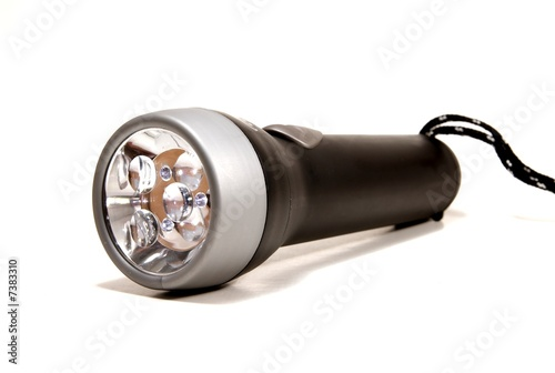 a black flashlight torch on a white seemless background.