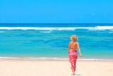 Girl in bikini and pareo walking towards ocean poster