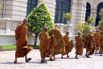 monks walking in line dressed in saffron robes