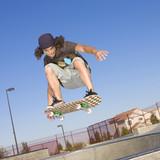 Fototapety Skateboard tricks at a skateboard park