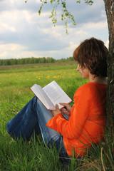 Young women read book in garden