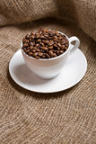 Cup with freshly roasted coffee beans on sackcloth