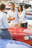 Young couple discussing new car with salesman