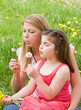 Mother and Daughter Blowing Dandelion Seeds Together