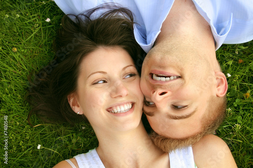 young and happy couple is smiling on a meadow