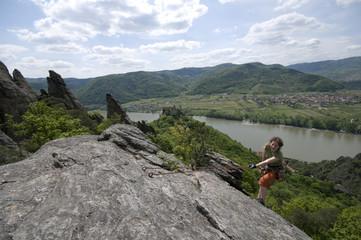 Bergsteigerin seilt sich lachend von einem Felsen ab