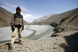 hiker standing in front of river valley , annapurna poster