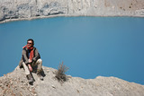 trekker sitting on mountain summit with blue lake in background poster