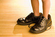 Big shoes to fill, child's feet in large black shoes, on wood fl - 7526357