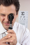 Eye doctor using opthalmoscope poster
