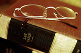 Closeup of eye glasses on top of legal books poster