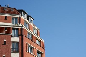 Immeuble en brique rouges avec vue sur ciel bleu