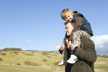 A father carries his son on his shoulders.
