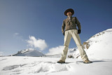 man standing in snow with legs apart, annapurna, nepal poster