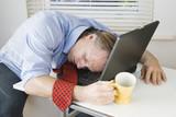 An exhausted businessman falls asleep on computer. poster