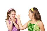 Two young girls fighting one slapping the other and one scared