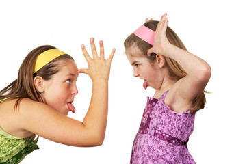 Two young girls fighting and sticking tout heir tongues out