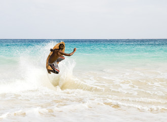 A skimboarder jumps a wave.