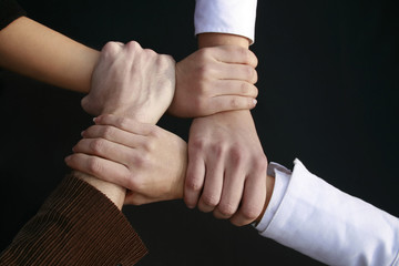 four hands holding tight together on black