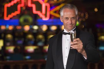 Man in tuxedo drinking champagne in casino