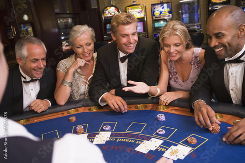 Group of friends playing blackjack in casino - 7576578