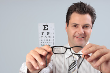 Optometrist holding eyeglasses frames for customer