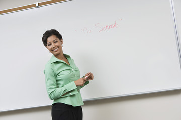 Business woman standing in front of whiteboard, laughing