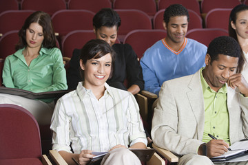 People sitting in auditorium and clapping hands