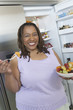 Woman eating salad by open fridge