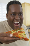Portrait of man eating pizza