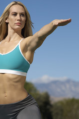 Young woman with arm extended, exercising outdoors