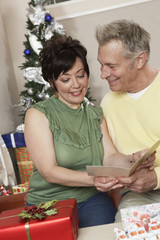 Senior couple looking at card over Christmas presents