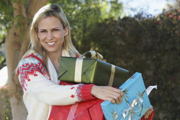 Woman carrying presents outside, portrait
