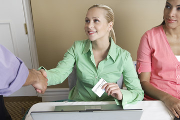 Receptionist distributing name tags