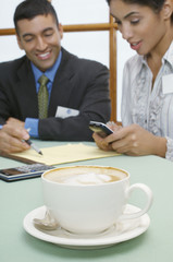 Business man and woman at cafe, focus on cappuccino in foreground