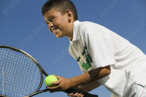 Young boy on tennis court Preparing to Serve, close up, low angle view
