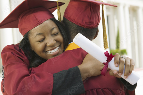 Two graduates hugging outside